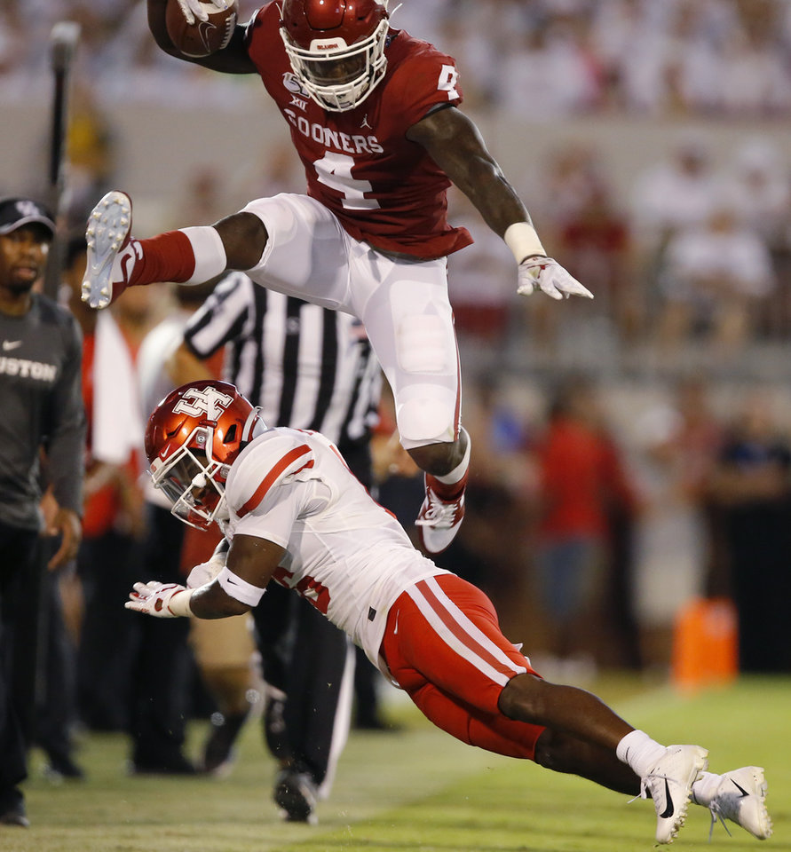 Photo - Oklahoma's Trey Sermon (4) leaps over Houston's Ka'Darian Smith (16) during a college football game between the University of Oklahoma Sooners (OU) and the Houston Cougars at Gaylord Family-Oklahoma Memorial Stadium in Norman, Okla., Sunday, Sept. 1, 2019. [Bryan Terry/The Oklahoman]