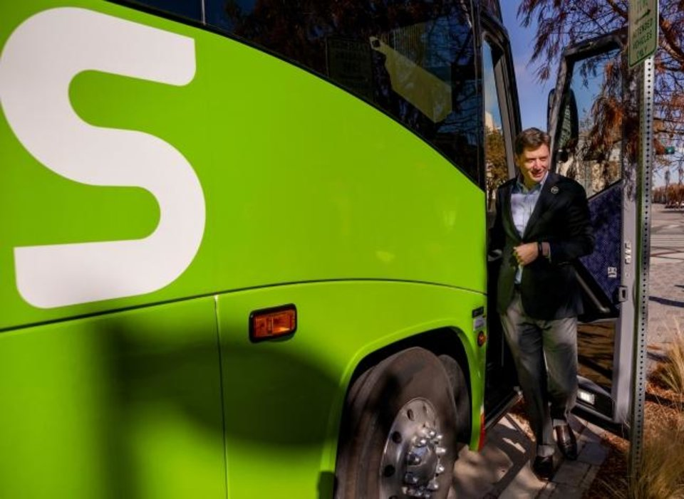 Photo -  Mayor David Holt steps off the new FlixBus after the announcement ceremony.  [Chris Landsberger/The Oklahoman]
