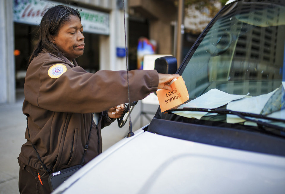 Photo -  Oklahoma City Police Service Technician Marsha Nealy issues a parking ticket in downtown Oklahoma City. [Photo by Chris Landsberger, The Oklahoman]