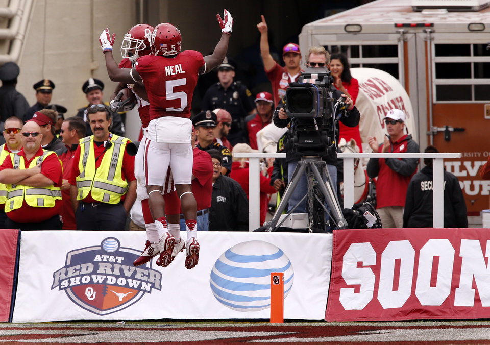 Photo - Oklahoma's Durron Neal (5) celebrates with Samaje Perine (32) on Perine's score during the second half of the Red River Showdown college football game between the University of Oklahoma Sooners (OU) and the University of Texas Longhorns (UT) at the Cotton Bowl in Dallas, Texas on Saturday, Oct. 11, 2014. 