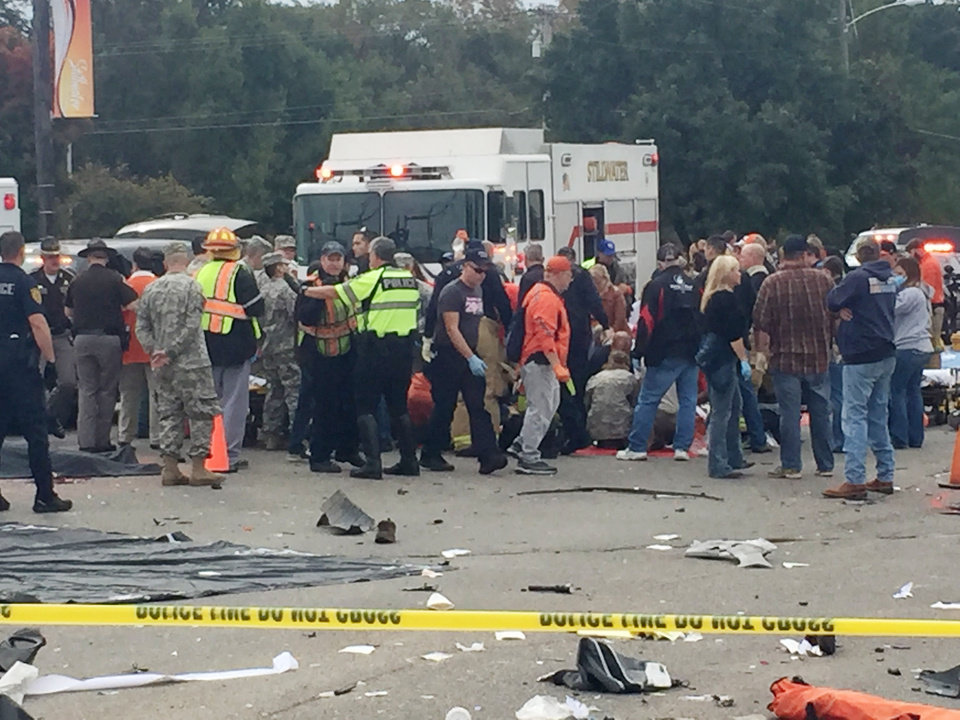 Photo - People work tend to the injured at the scene of a fatal crash at the intersection of Main and Hall of Fame during the Oklahoma State University (OSU) homecoming parade in Stillwater, Okla., Saturday, Oct. 24, 2015. Photo by Zach Gray, For The Oklahoman