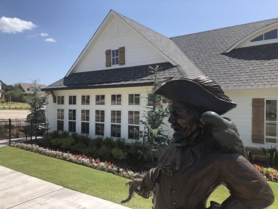 Photo -  A pirate with parrot, public statuary, stands outside the clubhouse in Town Square addition in Edmond.  [RICHARD MIZE/THE OKLAHOMAN]
