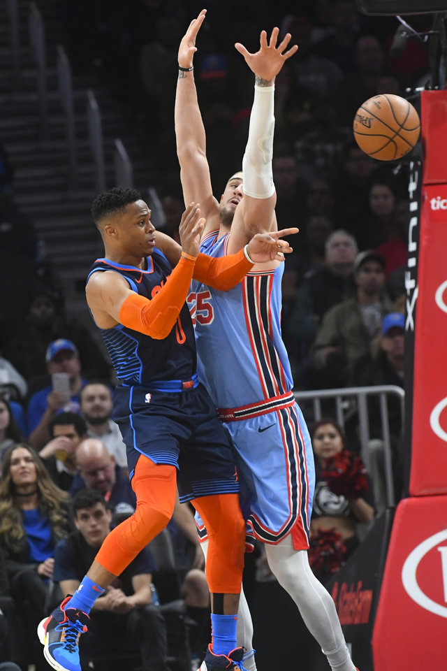Photo - Oklahoma City Thunder guard Russell Westbrook passes as Atlanta Hawks center Alex Len, right, defends during the first half of an NBA basketball game, Tuesday, Jan. 15, 2019, in Atlanta. (AP Photo/John Amis)