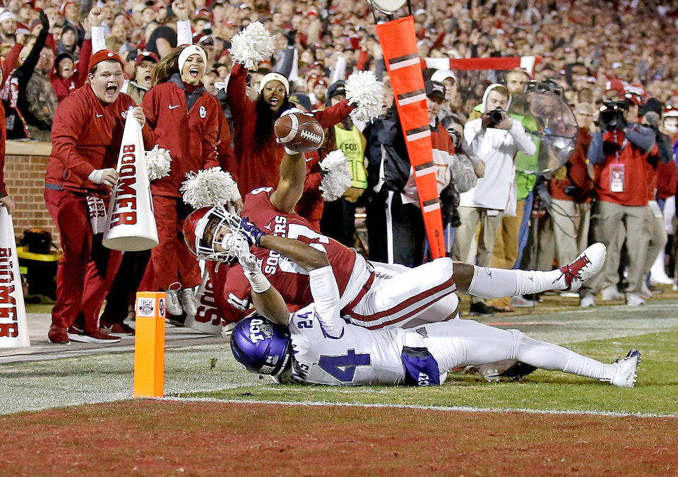 Photo - Oklahoma's Brayden Willis (81) stretches for a touchdown as TCU's Julius Lewis (24) defends in the first quarter during an NCAA football game between the University of Oklahoma Sooners (OU) and the TCU Horned Frogs at Gaylord Family-Oklahoma Memorial Stadium in Norman, Okla., Saturday, Nov. 23, 2019. [Sarah Phipps/The Oklahoman]