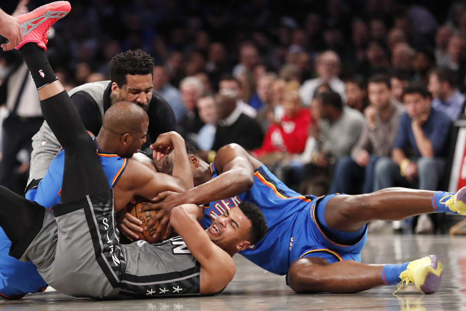 Photo - Brooklyn Nets guard Timothe Luwawu-Cabarrot (9) struggles to control the ball a he engages in a floor scramble with Oklahoma City Thunder guard Chris Paul, left, and Thunder guard Deonte Burton (30) during the first half of an NBA basketball game, Tuesday, Jan. 7, 2020, in New York. Nets forward Wilson Chandler, upper left, gets in on the tug-of-war. (AP Photo/Kathy Willens)