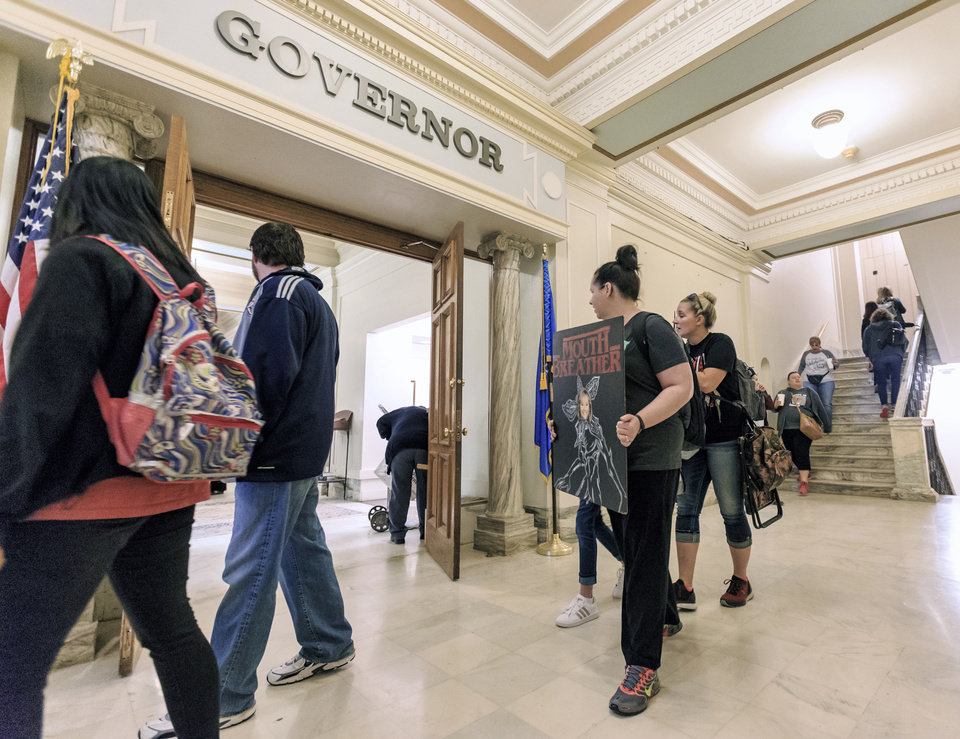 Photo - Teacher walk past the Governor's office during the ninth day of a walkout by Oklahoma teachers at the state Capitol in Oklahoma City, Okla. on Tuesday, April 10, 2018.   Photo by Chris Landsberger, The Oklahoman