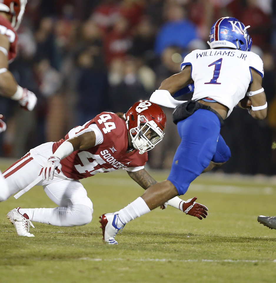 Photo - Kansas' Pooka Williams Jr. (1) gets past Oklahoma's Brendan Radley-Hiles (44) during a college football game between the University of Oklahoma Sooners (OU) and the Kansas Jayhawks (KU) at Gaylord Family-Oklahoma Memorial Stadium in Norman, Okla., Saturday, Nov. 17, 2018. Photo by Bryan Terry, The Oklahoman