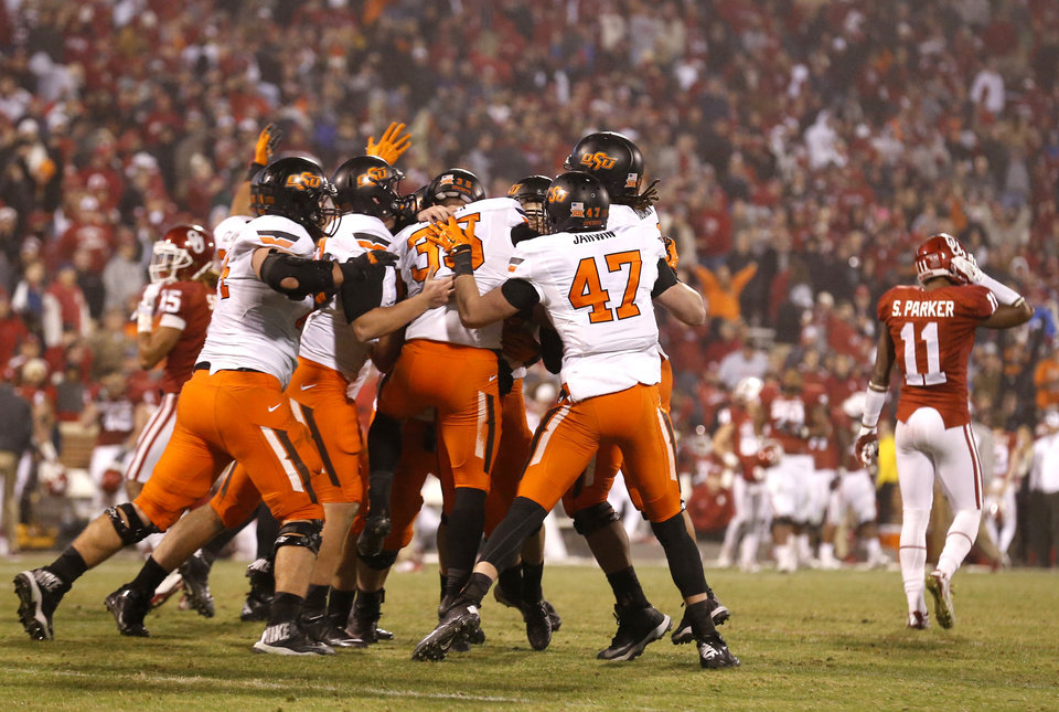 Photo - Oklahoma State celebrates Ben Grogan's (19) game wining field goal in overtime as Oklahoma's Steven Parker (11) walks off the field during the Bedlam college football game between the University of Oklahoma Sooners (OU) and the Oklahoma State Cowboys (OSU) at Gaylord Family-Oklahoma Memorial Stadium in Norman, Okla., Saturday, Dec. 6, 2014. Photo by Sarah Phipps, The Oklahoman