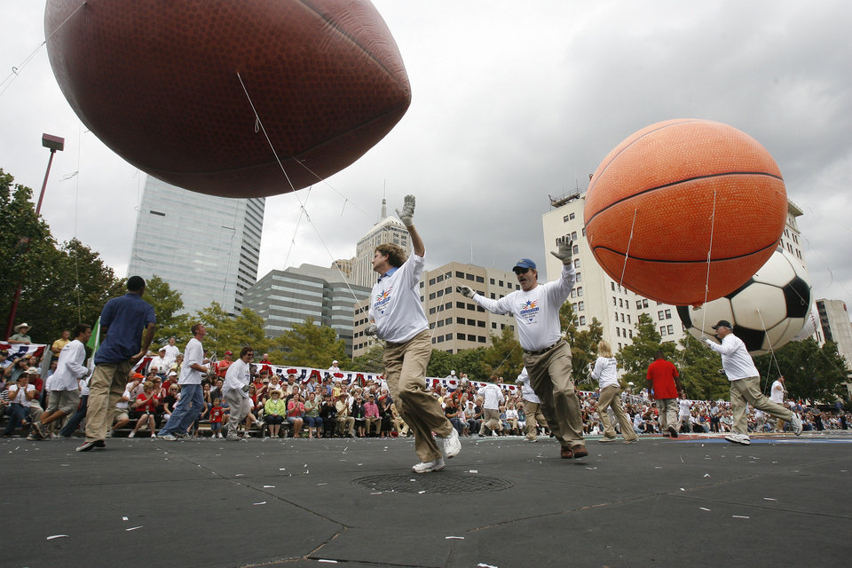 Photo - Handlers run circles under giant helium filled balls during the Oklahoma Centennial Parade in downtown Oklahoma City, Okla., Sunday, October 14, 2007. Photo by Paul Hellstern / The Oklahoman.