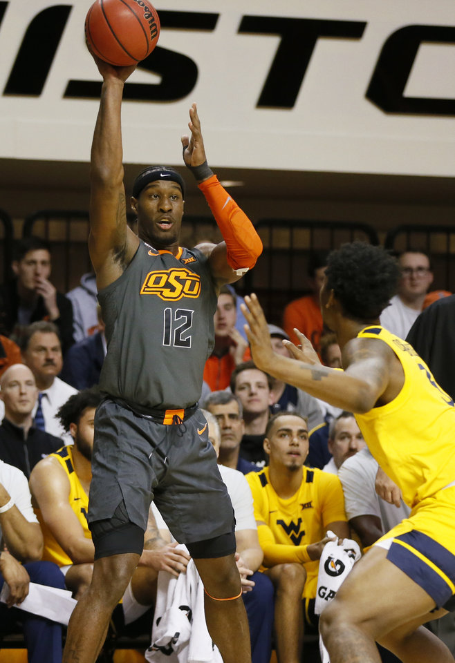 Photo - Oklahoma State's Cameron McGriff (12) passes in the first half during a men's college basketball game between the Oklahoma State Cowboys and West Virginia Mountaineers at Gallagher-Iba Arena in Stillwater, Okla., Monday, Jan. 6, 2020. [Nate Billings/The Oklahoman]