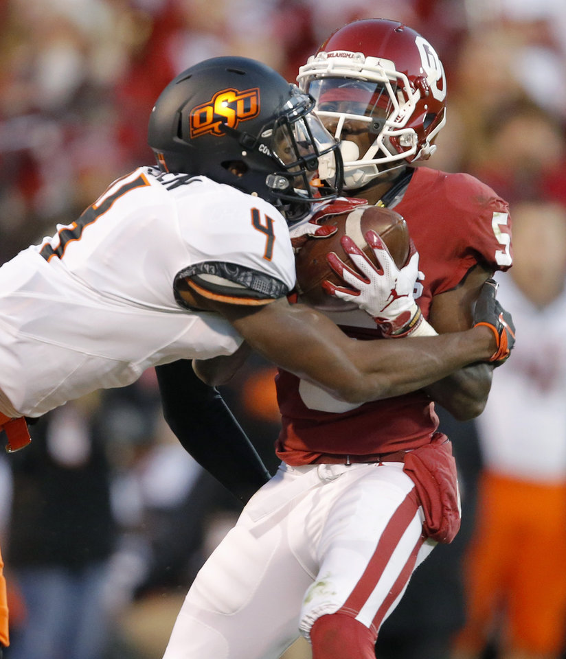 Photo - Oklahoma's Marquise Brown (5) catches a pass beside Oklahoma State's A.J. Green (4) during a Bedlam college football game between the University of Oklahoma Sooners (OU) and the Oklahoma State University Cowboys (OSU) at Gaylord Family-Oklahoma Memorial Stadium in Norman, Okla., Nov. 10, 2018.  Photo by Bryan Terry, The Oklahoman