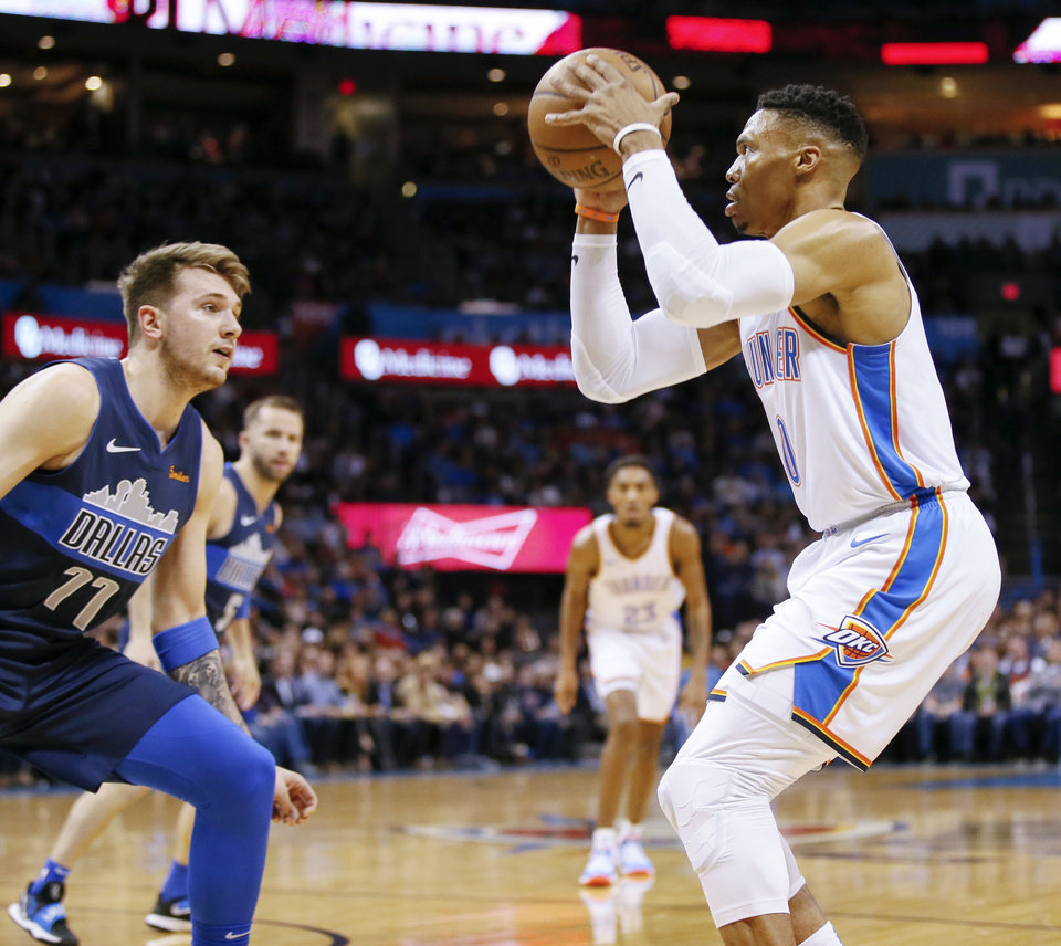 Photo - Oklahoma City's Russell Westbrook (0) pulls up to take shot in front of Dallas' Luka Doncic (77) during an NBA basketball game between the Oklahoma City Thunder and Dallas Mavericks at Chesapeake Energy Arena in Oklahoma City, Monday, Dec. 31, 2018. Photo by Nate Billings, The Oklahoman