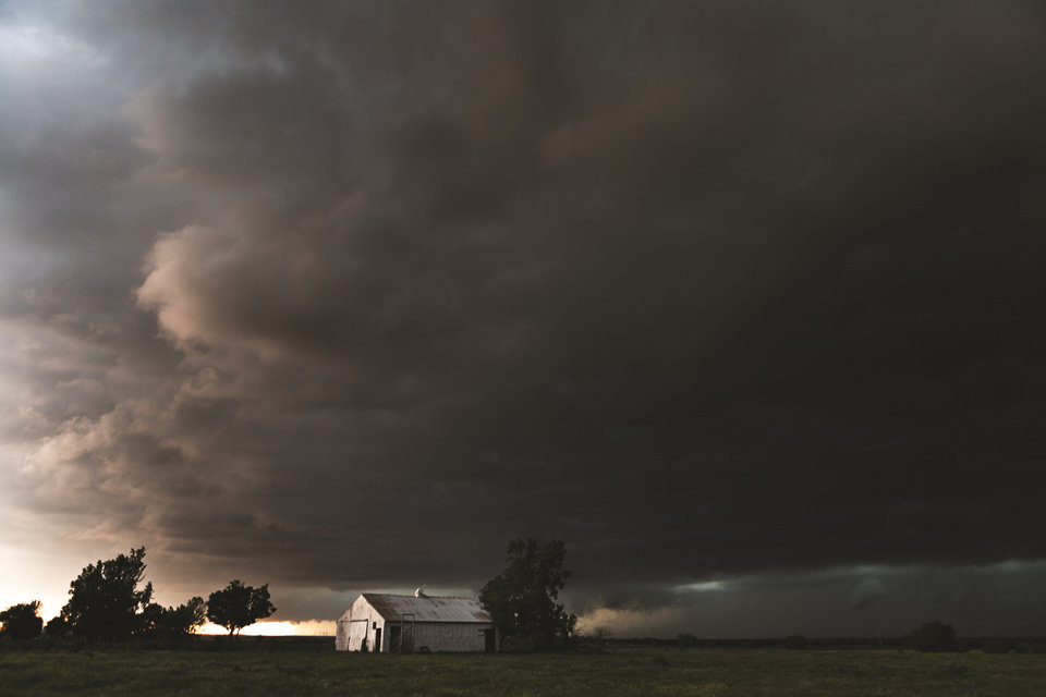 Photo -  Dark skies hover over a barn in Oklahoma in May 2013. [Photo by Camille Seaman]