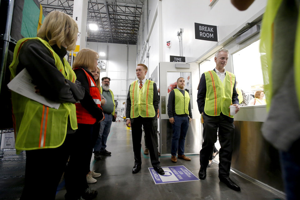 Photo - U.S. Sen. James Lankford, center U.S. Rep. Steve Russell, at right, tour the new new Amazon Delivery Center in Oklahoma City, Tuesday, Oct. 23, 2018. Photo by Bryan Terry, The Oklahoman