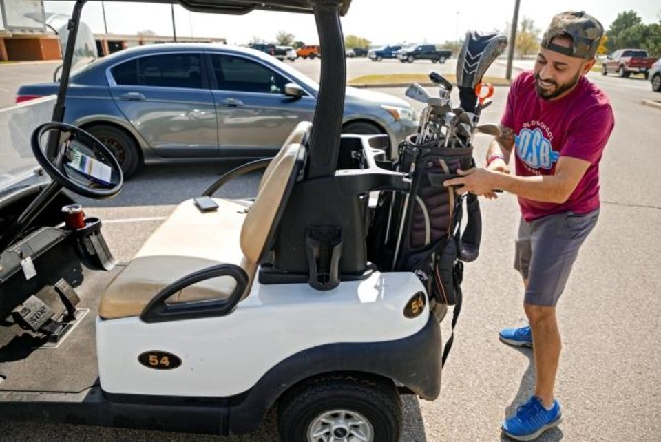 Photo -  Tarek Amaireh loads up his cart as he prepares to play a round of golf Friday at Lake Hefner Golf Club. [Chris Landsberger/The Oklahoman]
