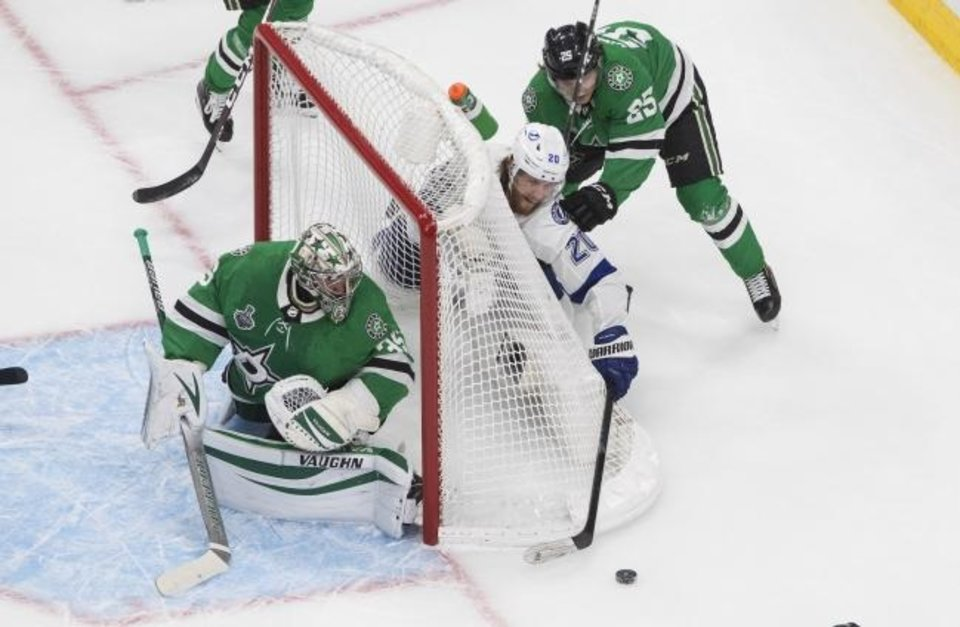 Photo -  Dallas Stars goaltender Anton Khudobin (35) looks back for the puck as Tampa Bay Lightning center Blake Coleman (20) and Stars left wing Joel Kiviranta (25) work behind the net during the second period of Wednesday's Game 3 of the NHL hockey Stanley Cup Final in Edmonton, Alberta. [Jason Franson/The Canadian Press via AP]