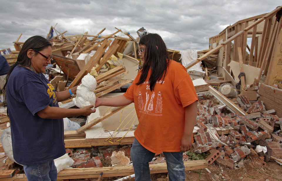 Photo - Ella Sleeper finds one of her mother Susan's favorite items out of the rubble left behind by Tuesday's tornado west of El Reno, Wednesday, May 25, 2011. Photo by Chris Landsberger, The Oklahoman