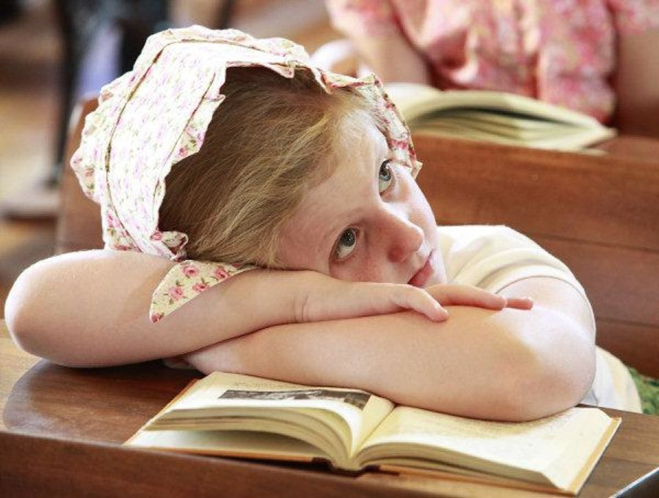 Photo - Reagan Baskin, 8, rests her head on her McGuffey's reader while listening to the teacher read Wednesday during 1889 Summer Camp at Edmond's historic school house. PHOTO BY DAVID MCDANIEL, THE OKLAHOMAN  David McDaniel
