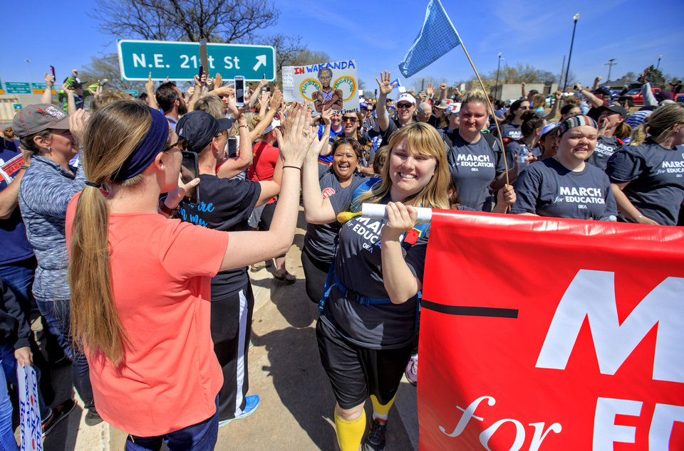 Photo - Supporters give out high fives as teachers arrive at the Capitol as they finish their 110 mile walk from Tulsa during the ninth day of a walkout by Oklahoma teachers at the state Capitol in Oklahoma City, Okla. on Tuesday, April 10, 2018.   Photo by Chris Landsberger, The Oklahoman