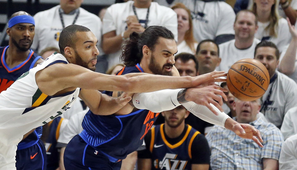 Photo - Utah Jazz center Rudy Gobert, left and Oklahoma City Thunder center Steven Adams, right, reach for a loose ball in the first half during Game 4 of an NBA basketball first-round playoff series Monday, April 23, 2018, in Salt Lake City. (AP Photo/Rick Bowmer)