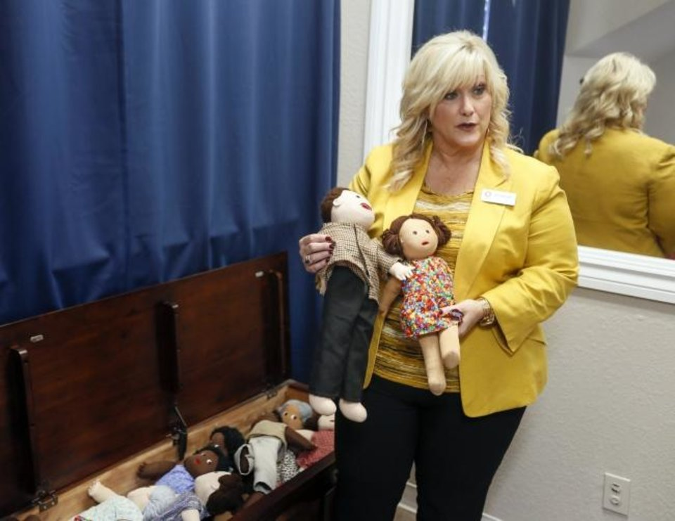 Photo -  Stacy McNeiland holds dolls used in forensic interviews in the interview room at the Care Center, 1403 Ashton Place. McNeiland is the CEO of the center. [Nate Billings/The Oklahoman]