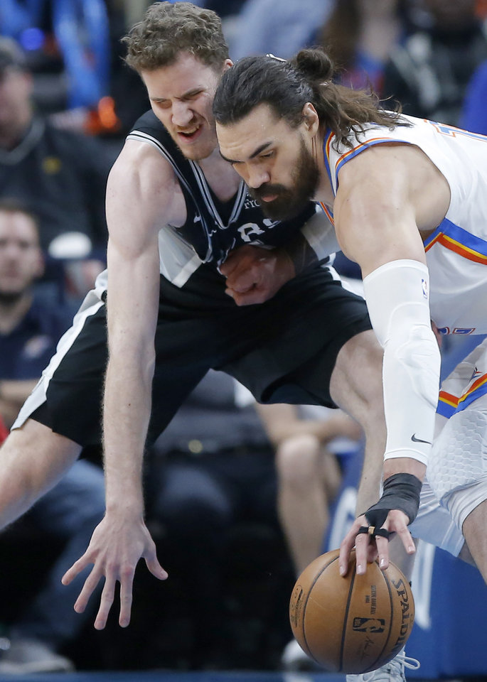Photo - Oklahoma City's Steven Adams (12) reaches for the ball beside San Antonio's Jakob Poeltl (25) during an NBA basketball game between the Oklahoma City Thunder and the San Antonio Spurs at Chesapeake Energy Arena in Oklahoma City, Tuesday, Feb. 11, 2020. [Bryan Terry/The Oklahoman]