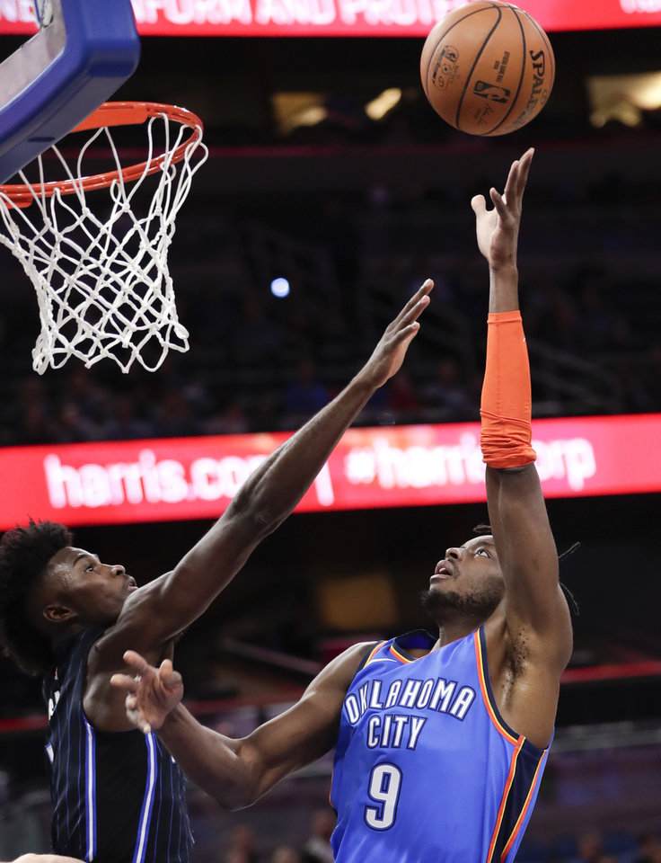 Photo - Oklahoma City Thunder's Jerami Grant (9) makes a shot over Orlando Magic's Jonathan Isaac, left, during the first half of an NBA basketball game, Tuesday, Jan. 29, 2019, in Orlando, Fla. (AP Photo/John Raoux)