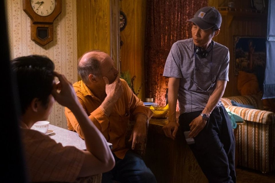 Photo - Director and writer Lee Isaac Chung, right, talks with actors  Steven Yeun, left, and Will Patton on the set of