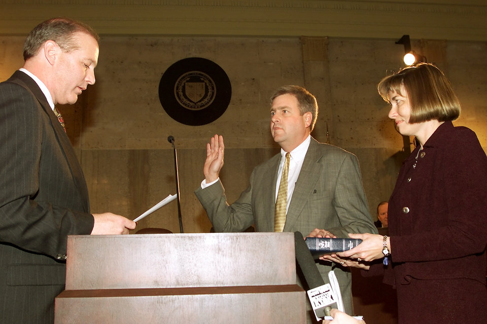 Photo -  In 2000, outgoing City Manager Glenn Deck, left, administers the oath of office to incoming City Manager Jim Couch, as Couch's wife, Cathy, holds the Bible. [Photo by Doug Hoke, The Oklahoman Archives]