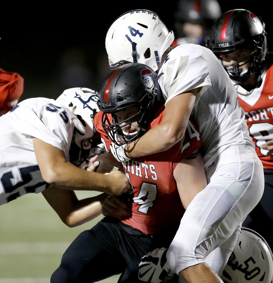 Photo - Jacob Snyder of Crossings is brought down by Minco's Cashus Burchfield, right, and Orlando Vazquez during a high school football game between Crossings Christian and Minco in Oklahoma City, Friday, Sept. 13, 2019. [Bryan Terry/The Oklahoman]