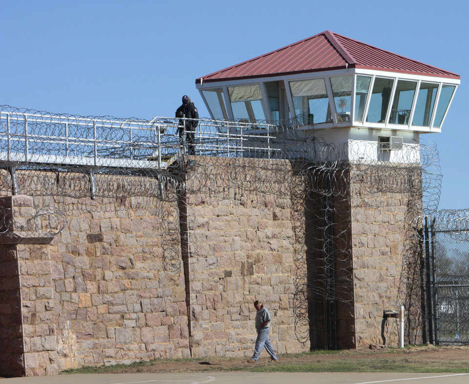 Photo - An inmate walks in the yard under a guard at the Oklahoma State Reformatory in Granite, Tuesday, Oklahoma, November 12, 2013. Photo by David McDaniel, The Oklahoman  David McDaniel - The Oklahoman
