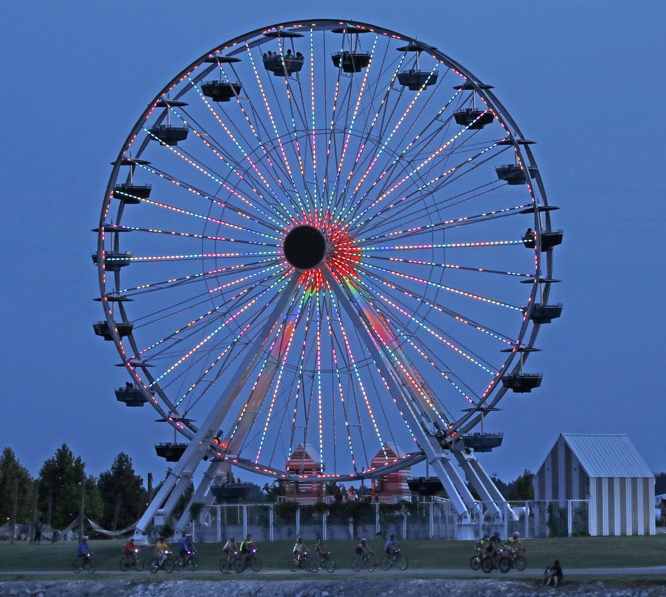 Photo - The full moon bike ride goes by the Wheeler Park Ferris Wheel on the south shore of the Oklahoma River Tuesday, July 16, 2019. [THE OKLAHOMAN ARCHIVES]