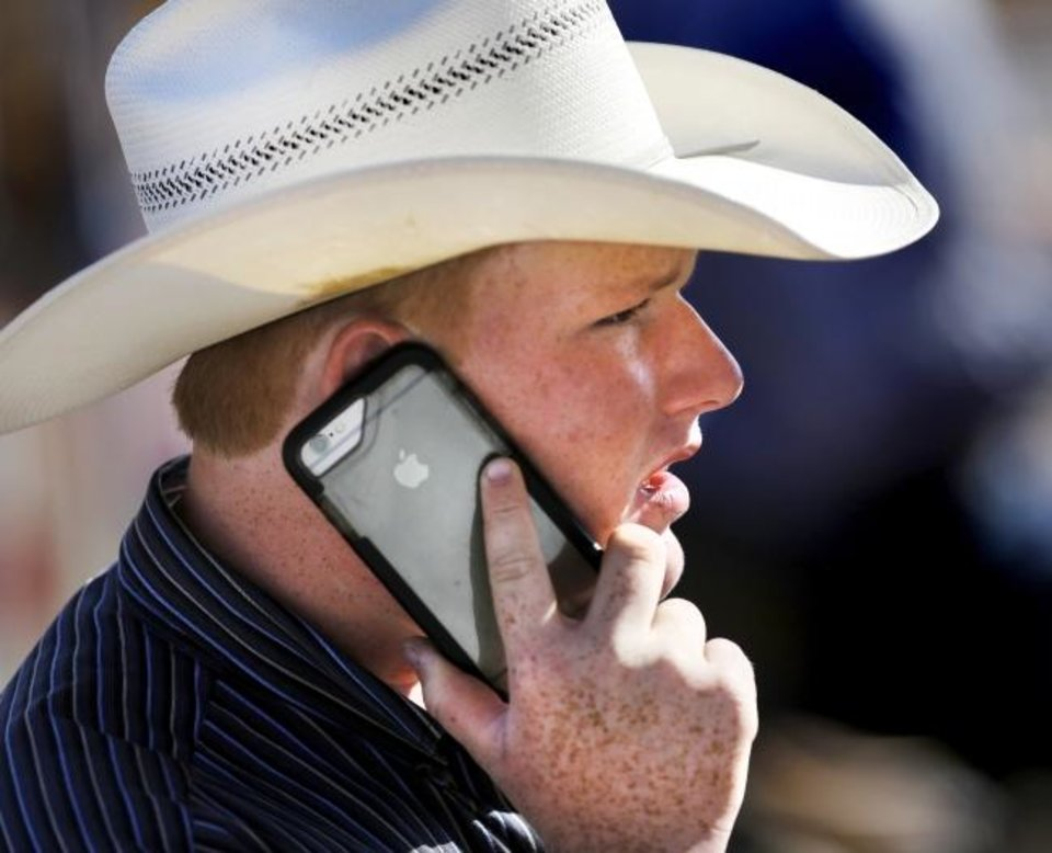 Photo -  Mobile phones, like this one being used by a cowboy at the IFYR Rodeo in Shawnee in 2017, have become a preferred way for people to communicate. [THE OKLAHOMAN ARCHIVES]