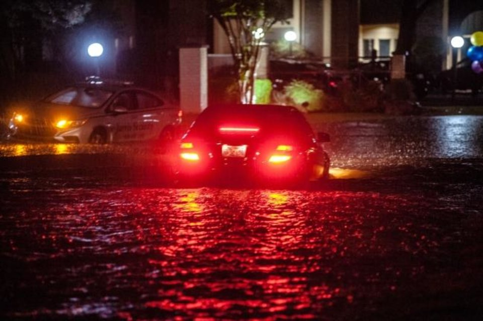 Photo -  A car drives through floodwaters covering E 54th Street near Yale Avenue as heavy rains cause flash flooding across Tulsa on Tuesday. [Joeph Rushmore/for the Tulsa World]