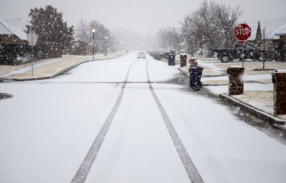 Photo - Snow collects on a neighborhood roadway as a winter storm makes its way into Oklahoma City, Okla. on Thursday, Jan. 3, 2019. Photo by Chris Landsberger, The Oklahoman