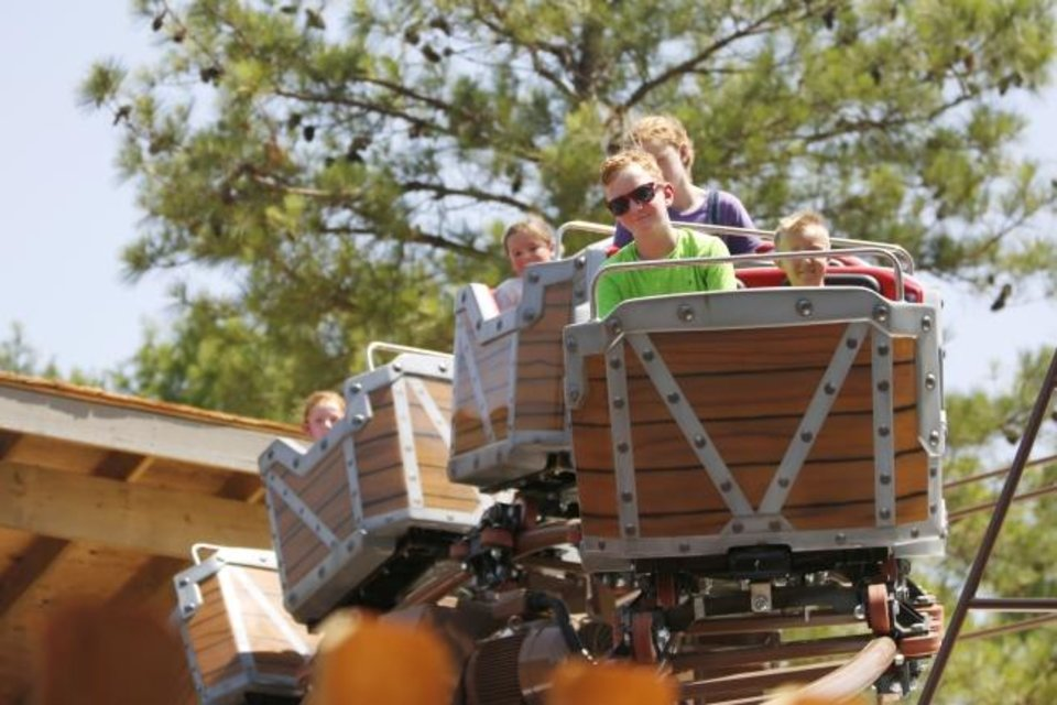 Photo -  John Mankin, 9, rides Frankie's Mine Train on June 28 in the newly revamped Timber Town kids area of Frontier City in Oklahoma City. [Paxson Haws/The Oklahoman]