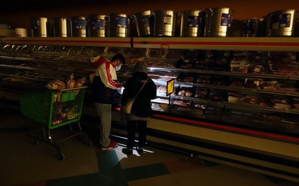 Photo -  FILE - In this Feb. 16, 2021, file photo, customers use the light from a cell phone to look in the meat section of a grocery store in Dallas. Even though the store lost power, it was open for cash only sales. (AP Photo/LM Otero, File)