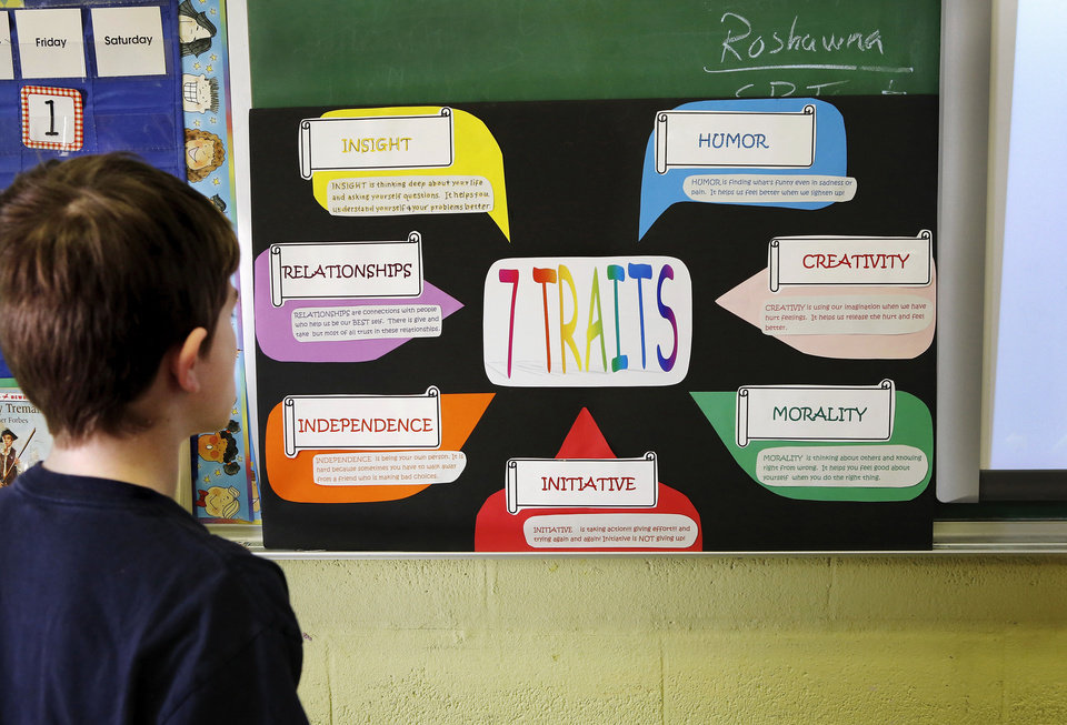 Photo - Devven (cq) looks at this poster to study details listed for the seven traits before he composes his poem.   Some students at Positive Tomorrows, a school for homeless children,  participate in the
