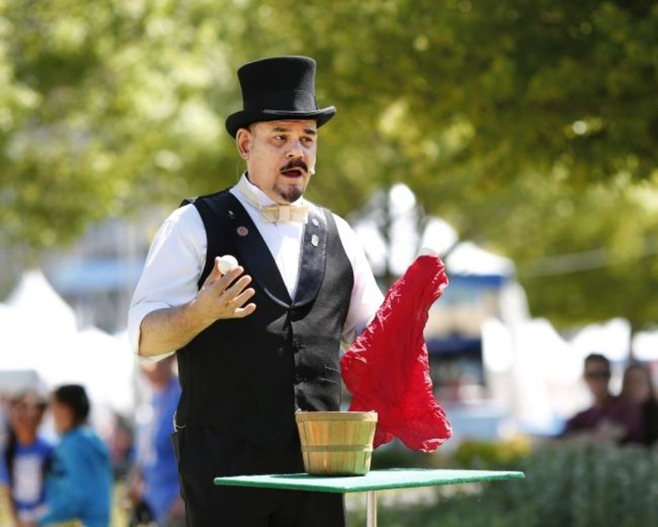 Photo -  Capstone the Magician, the street performer at this year's Festival of the Arts, does a trick during a Thursday afternoon performance at the downtown Oklahoma City event. He is performing 40-minute sets at  at noon, 2:30 and 7:45 p.m. Friday and Saturday; and at noon, 2 and 4 p.m. Sunday.  Performances are on the Colcord Lawn at Bicentennial Park, near the Civic Center.   [Jim Beckel/The Oklahoman]