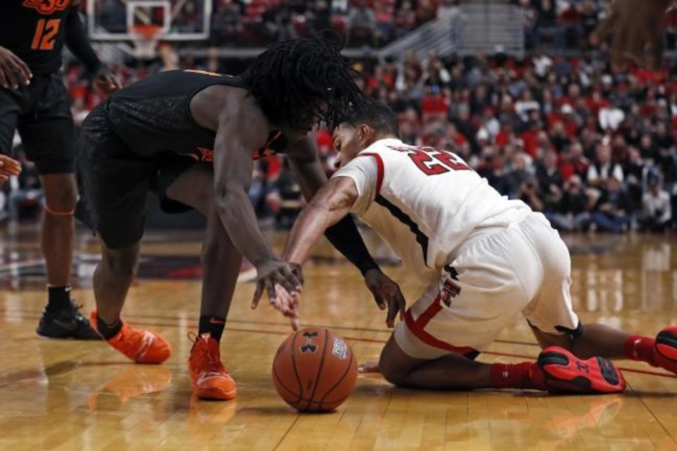 Photo -  Texas Tech's TJ Holyfield, right, knocks the ball away from Oklahoma State's Isaac Likekele on Saturday. OSU will play No. 16 West Virginia at 8 p.m. Monday in Stillwater. [AP Photo/Brad Tollefson]