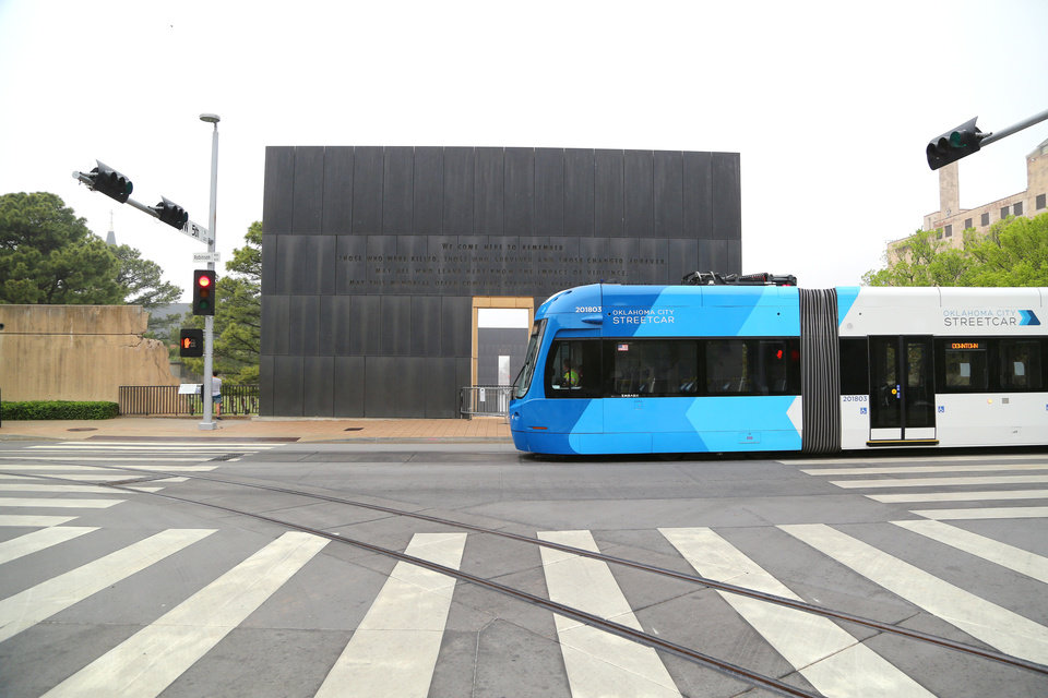 Photo - An Oklahoma City Streetcar goes by the 9:01 Gate of Time on the east side of the Oklahoma City National Memorial and Museum on the 25th anniversary of the bombing of the Alfred P. Murrah Federal Building, in Oklahoma City, Sunday, April 19, 2020. The memorial remains closed and did not hold a live remembrance ceremony because of the coronavirus pandemic. [Doug Hoke/The Oklahoman]
