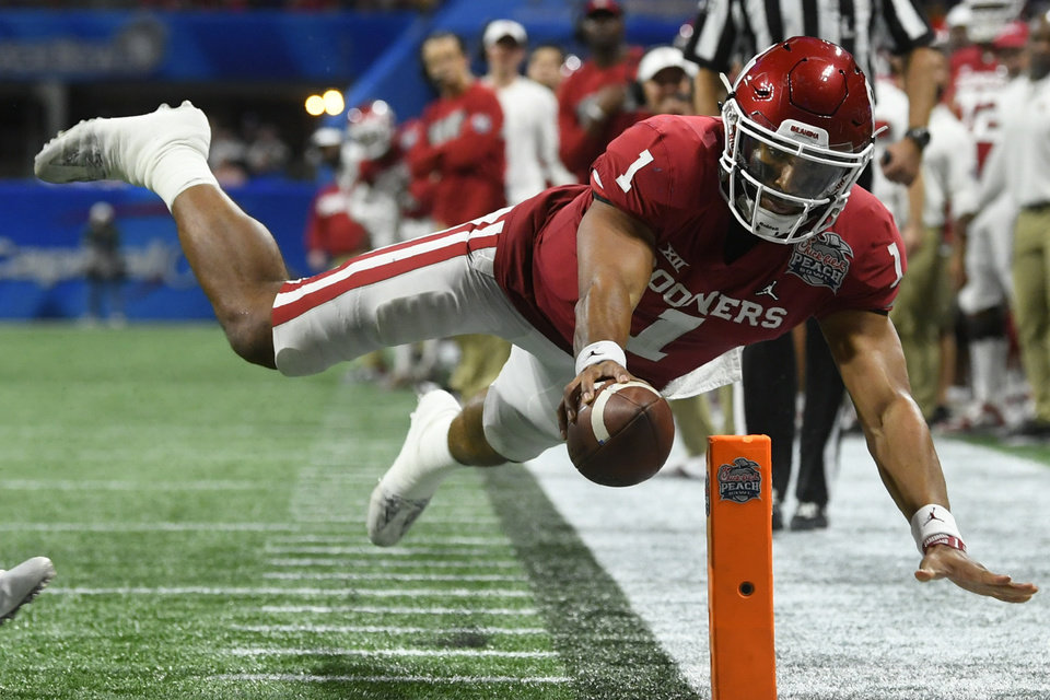 Photo - Oklahoma quarterback Jalen Hurts (1) scores a touchdown against LSU during the second half of the Peach Bowl NCAA semifinal college football playoff game, Saturday, Dec. 28, 2019, in Atlanta. (AP Photo/John Amis)