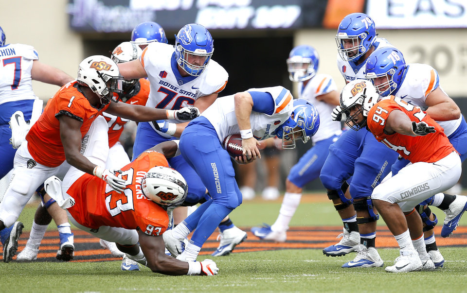 Photo - Oklahoma State's Jarrell Owens (93) sacks Boise State's Brett Rypien (4) as Oklahoma State's Calvin Bundage (1) and Jordan Brailford (94) add pressure during a college football game between the Oklahoma State Cowboys (OSU) and the Boise State Broncos at Boone Pickens Stadium in Stillwater, Okla., Saturday, Sept. 15, 2018. Photo by Sarah Phipps, The Oklahoman