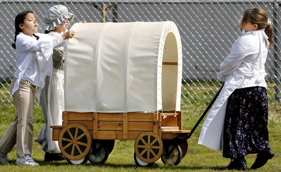 Photo - Three girls pull and push their covered wagon to the starting line at a 2007 Land Run re-enactment at Townsend Elementary School in Del City.  Photo by Jim Beckel, The Oklahoman Archives  JIM BECKEL -
