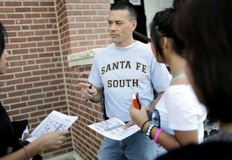 Photo - Superintendent Chris Brewster talks with students about their class schedules outside the school during the Back 2 School Bash at Santa Fe South Charter High School in Oklahoma City on Aug. 1.   JOHN CLANTON - THE OKLAHOMAN