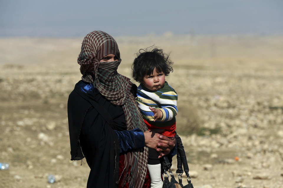 Photo - A displaced Iraqi mother and her child flee their home due to fighting between Iraqi special forces and Islamic State militants, on the western side of Mosul, Iraq, Thursday, Feb. 2017. The advance comes as part of a major assault that started five days earlier to drive Islamic State militants from the western half of Mosul, Iraq's second-largest city. (AP Photo/ Khalid Mohammed)