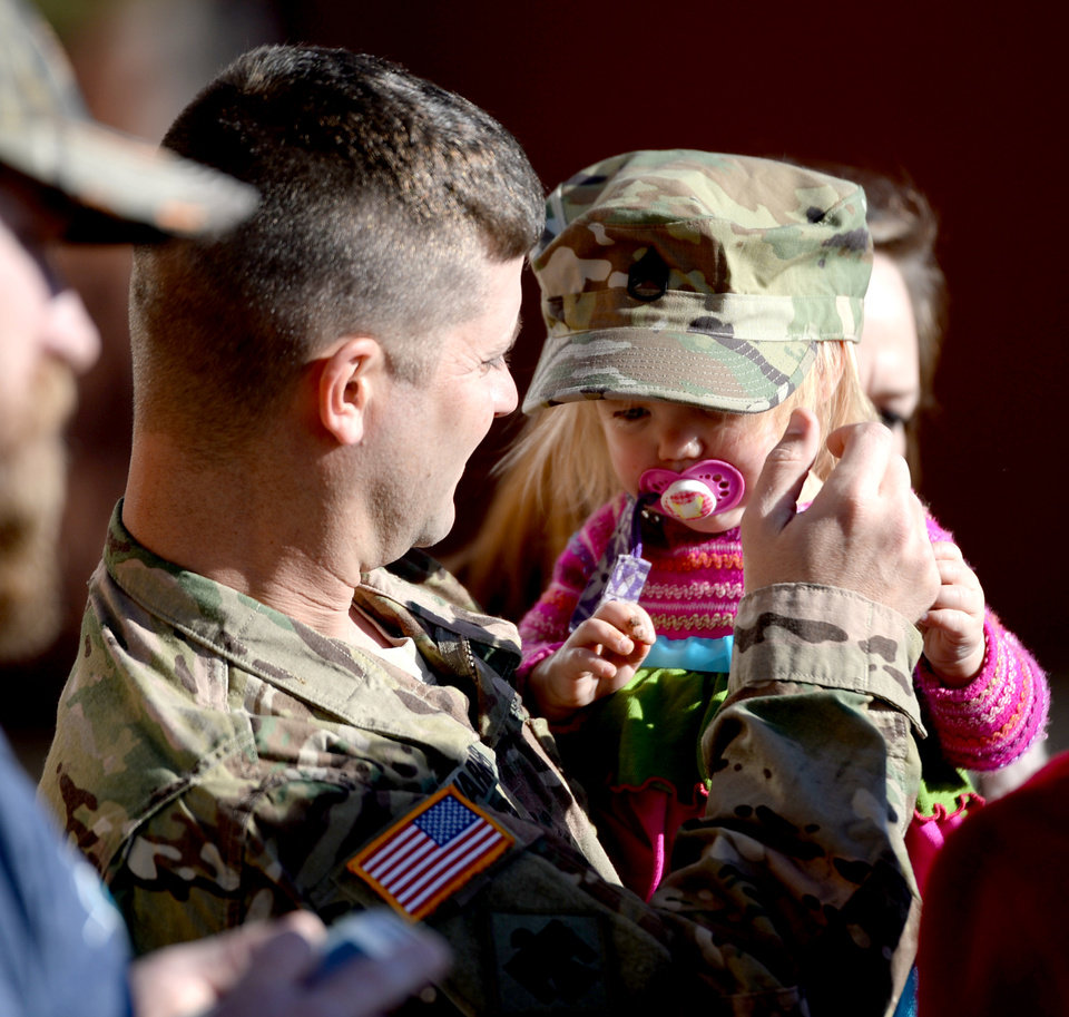 Photo -  Sgt. 1st Class Todd Warner places his hat on his daughter Gralyn's head during a sendoff ceremony for members of the Oklahoma National Guard's 1st Battalion, 179th Infantry Regiment at First Baptist Church of Moore. The battalion is deploying to Ukraine early next year. [Photo by Jackie Dobson, for The Oklahoman]