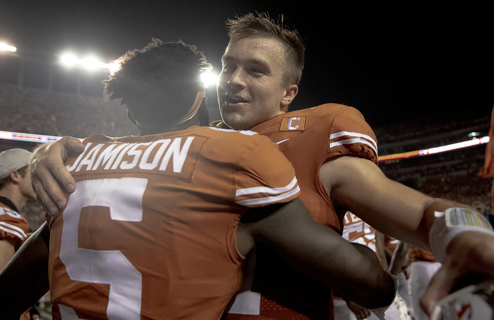 Photo - Texas quarterback Sam Ehlinger, right, hugs defensive back D'Shawn Jamison (5) following Texas' 36-30 win over Oklahoma in an NCAA college football game on Saturday, Sept. 21, 2019, in Austin, Texas. (Nick Wagner/Austin American-Statesman via AP)