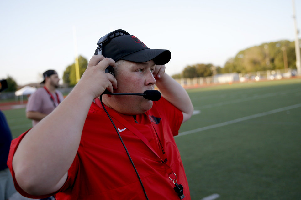 Photo - Del City coach Mike Dunn adjusts his headset during a high school football game between Del City and Bishop McGuinness in Del City, Okla., Friday, Sept. 6, 2019. [Bryan Terry/The Oklahoman]