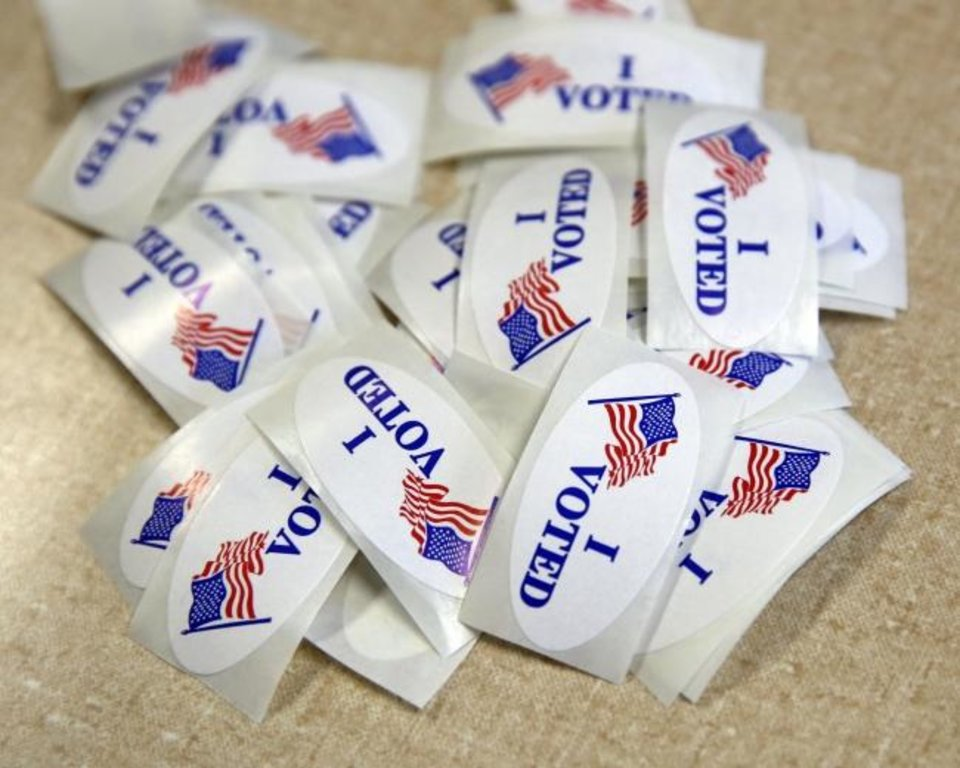 Photo -  Voting stickers are seen on a table in a polling place. [The Oklahoman Archives]
